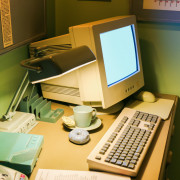 Retro office desk in dark room with simulator object.